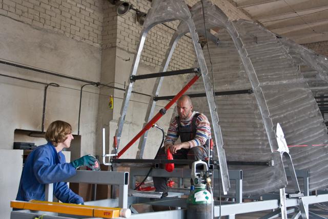 Missnöjd båtbyggare försöker få laserblupparna på rätt plats med hydraul.
